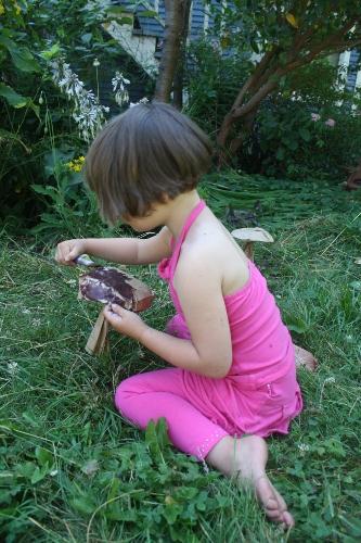 girl painting a paper mushroom