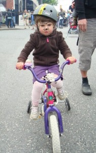 little girl on a bike with training wheels