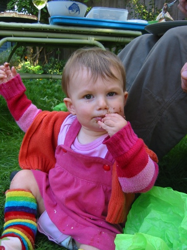 baby eating cake on her first birthday