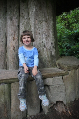 Little girl sitting on a bench beside a giant tree stump.