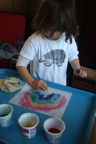 little girl painting a watercolour rainbow