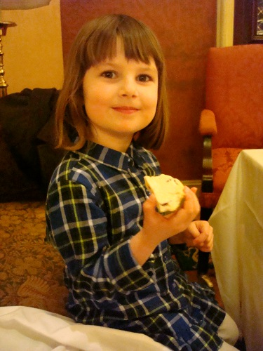 little girl eating a scone