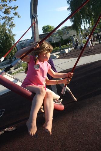little girl swinging on a disc swing