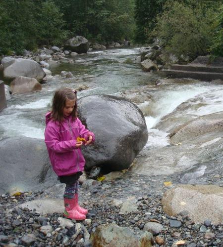 girl making leaf boats beside a fast river