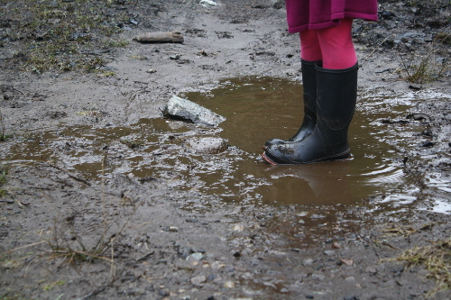 girl wearing rubber boots in a mud puddle