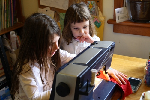 two girls using a sewing machine